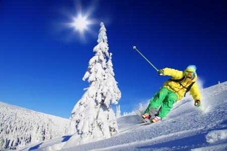 Lyžař na lyžích z kopce ve vysokých horách