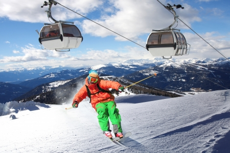 Skier skiing downhill in high mountains against cable railway photo