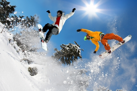 skier jumping: Snowboarders jumping against blue sky