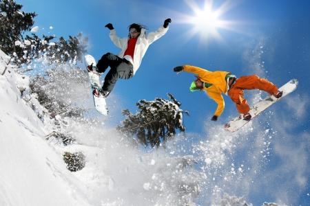 skieer: Snowboarders springen tegen de blauwe hemel