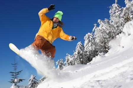 Snowboarder sautant contre le ciel bleu Banque d'images - 15383547