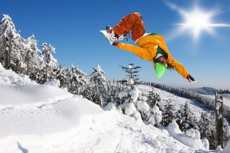 narciarz: Snowboarder jumping przeciw błękitne niebo