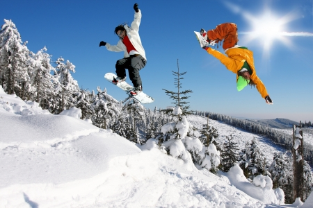 Snowboarders jumping against blue sky Stock Photo - 15383555