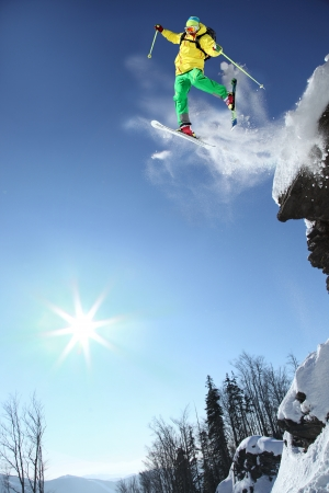 Skier jumping through the air from the rock