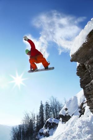 Snowboarder jumping against blue sky 版權商用圖片