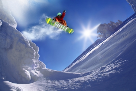 skieer: Snowboarder springen tegen blauwe hemel