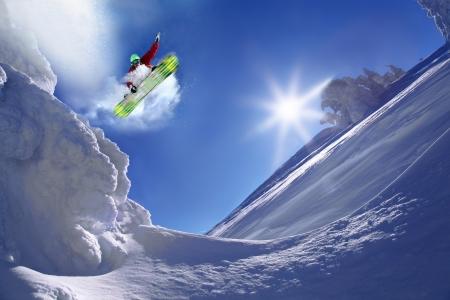 Snowboarder jumping gegen blauen Himmel Standard-Bild