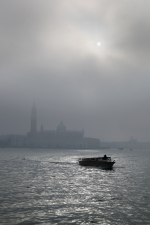 Venice with motor boat on Grand Canal in Italy during foggy morning photo