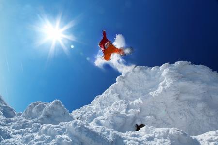 Snowboarder jumping against blue sky Foto de archivo