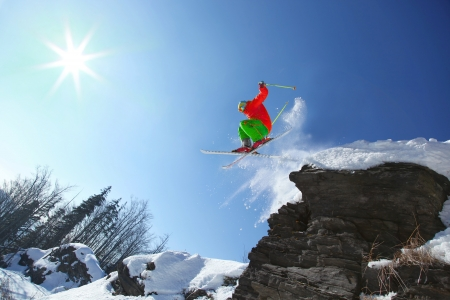 downhill skiing: Skier jumping against blue sky from the rock