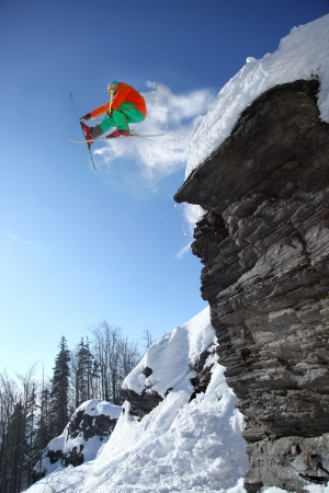 Skier jumping against blue sky from the rock photo