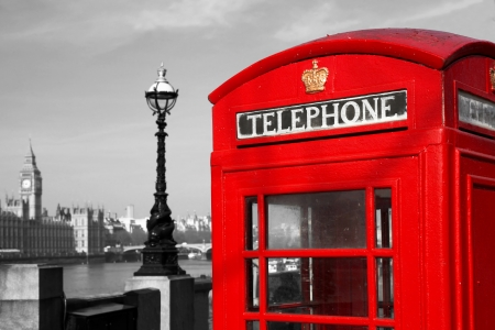 A traditional red phone booth in London against Big Ben, England photo