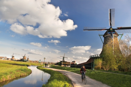 holland: Dutch windmills with bikers in Amsterdam, Holland