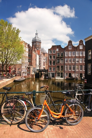 Amsterdam with bikes on the bridge over canal in Netherlands photo