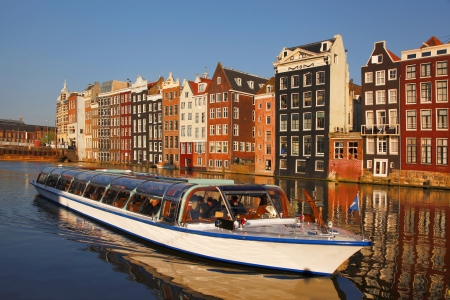 Amsterdam with tourist  boat on canal in Netherlands photo