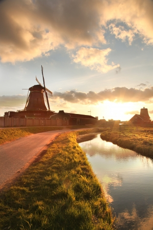 holland: Traditional Dutch windmills with canal against sunset in Amsterdam area, Holland