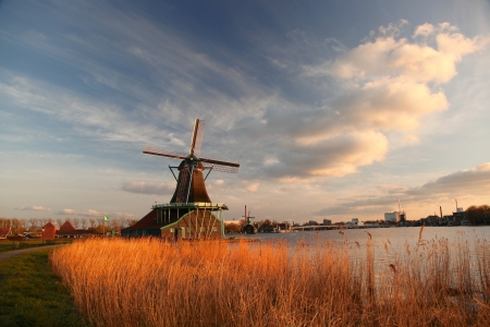 Traditional Dutch windmills with canal against sunset in Amsterdam area, Holland photo