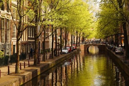 Amsterdam se zeleným kanálu v centru města, Holandska