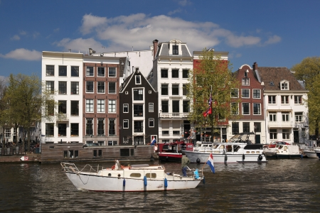 dutch landmark: Amsterdam city with boats on canal in Holland