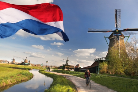 Windmills with flag of Holland in Zaanse Schans Stock Photo - 21483136
