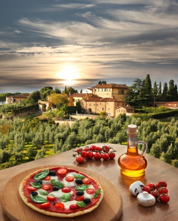 Italiaanse pizza in Chianti tegen olijfbomen en villa in Toscane, Italië