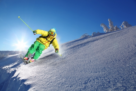 cliff jumping: Skier skiing downhill in high mountains