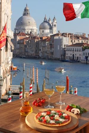 Klassieke Italiaanse pizza en glazen wijn in Venetië tegen Groot kanaal met boten, Italië