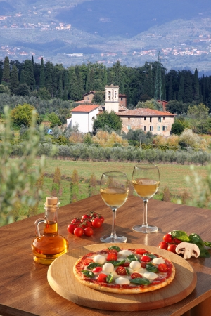 dring: Italian pizza and glasses of white wine in Chianti, famous vineyard landscape in Italy
