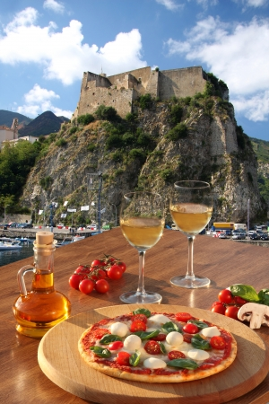 calabria: Italian pizza with glasses of wine against Scilla  Castle on the rock in Calabria, Italy