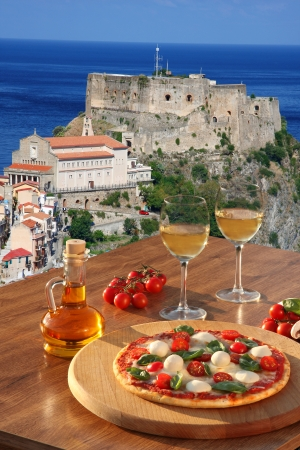 Italian pizza with glasses of wine against Scilla  Castle on the rock in Calabria, Italy