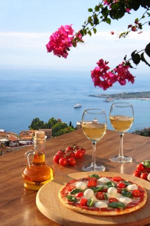 Taormina Dorf mit italienischer Pizza und Gläser Wein auf dem Tisch gegen Meerblick, Sizilien Insel, Italien