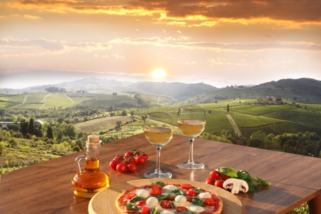 Italian pizza and glasses of white wine in Chianti, famous vineyard landscape in Italy