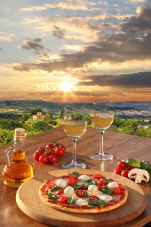 Italienische Pizza und Gläser Weißwein in Chianti, berühmt Weingut Landschaft in Italien