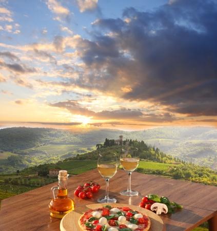 Italiaanse pizza en glazen witte wijn in Chianti, de beroemde wijngaard landschap in Italië