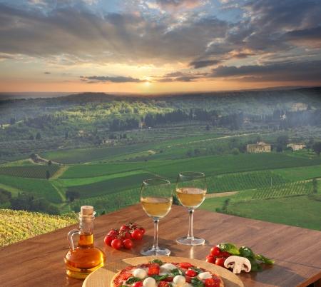 イタリアのピザとキャンティ、イタリアの有名なブドウ園の景色で白ワインのガラス