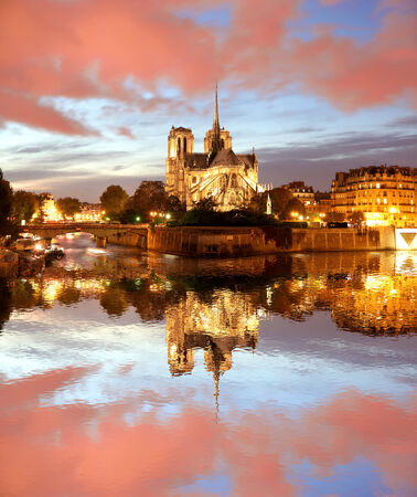 Notre Dame cathedral against sunset in Paris, France photo