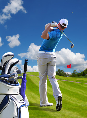 golf swing: Man playing golf against blue sky with golf bag Stock Photo
