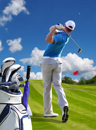 Man spielt Golf gegen blauen Himmel mit Golf-Bag Standard-Bild