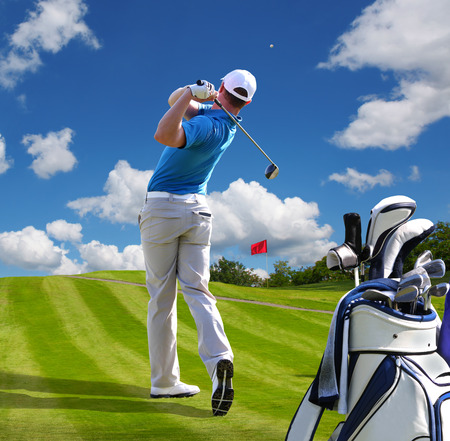 Man playing golf against blue sky with golf bag Stock Photo