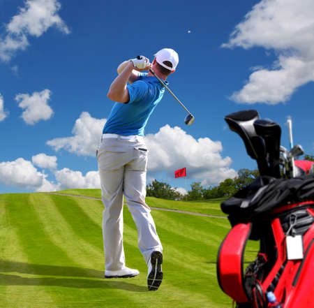 Man playing golf against blue sky with golf bag photo