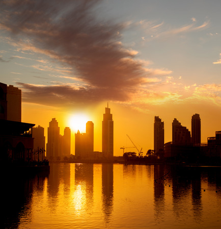 Dubai with golden silhouette of downtown against lagoon in United Arab Emirates photo