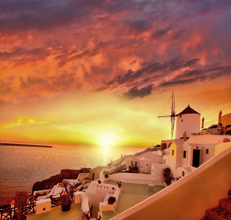 Windmill against colorful sunset, Santorini, Greece photo