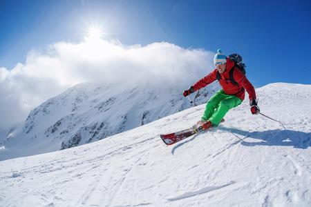 Skifahrer Ski-Abfahrt in den hohen Bergen vor Sonnenuntergang