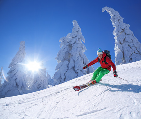Skier skiing downhill in high mountains against sunshine Stock Photo