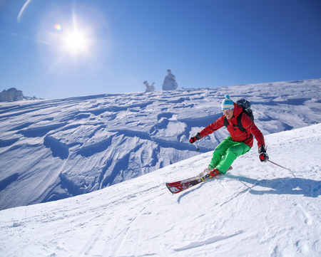 Skier skiing downhill in high mountains against sunshine photo