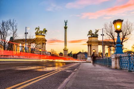 Denkmal auf dem Heldenplatz mit Brücke in Budapest gegen farbenprächtigen Sonnenuntergang, Ungarn