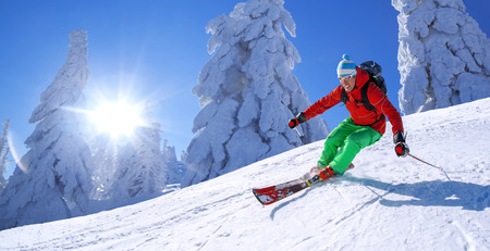snow ski: Skier skiing downhill in high mountains against blue sky