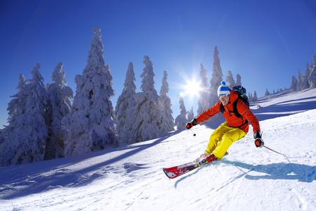 ski slopes: Skier skiing downhill in high mountains against sunset