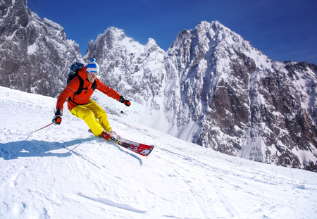 Skier skiing downhill in high mountains photo