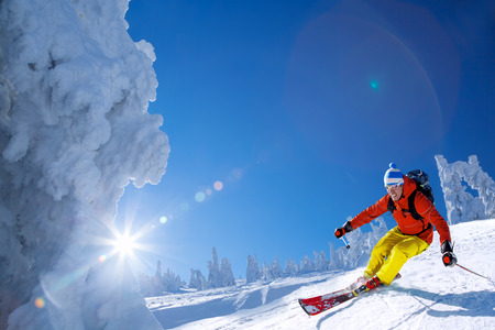 Skier skiing downhill in high mountains against blue sky photo